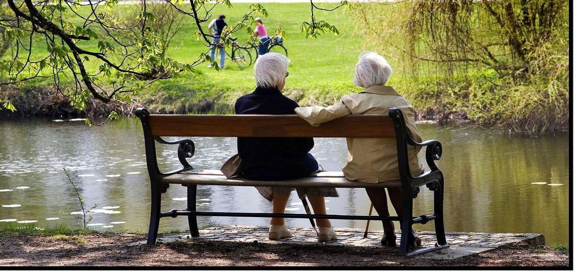 To ældre damer, der sidder på en bænk og kigger ud over en sø