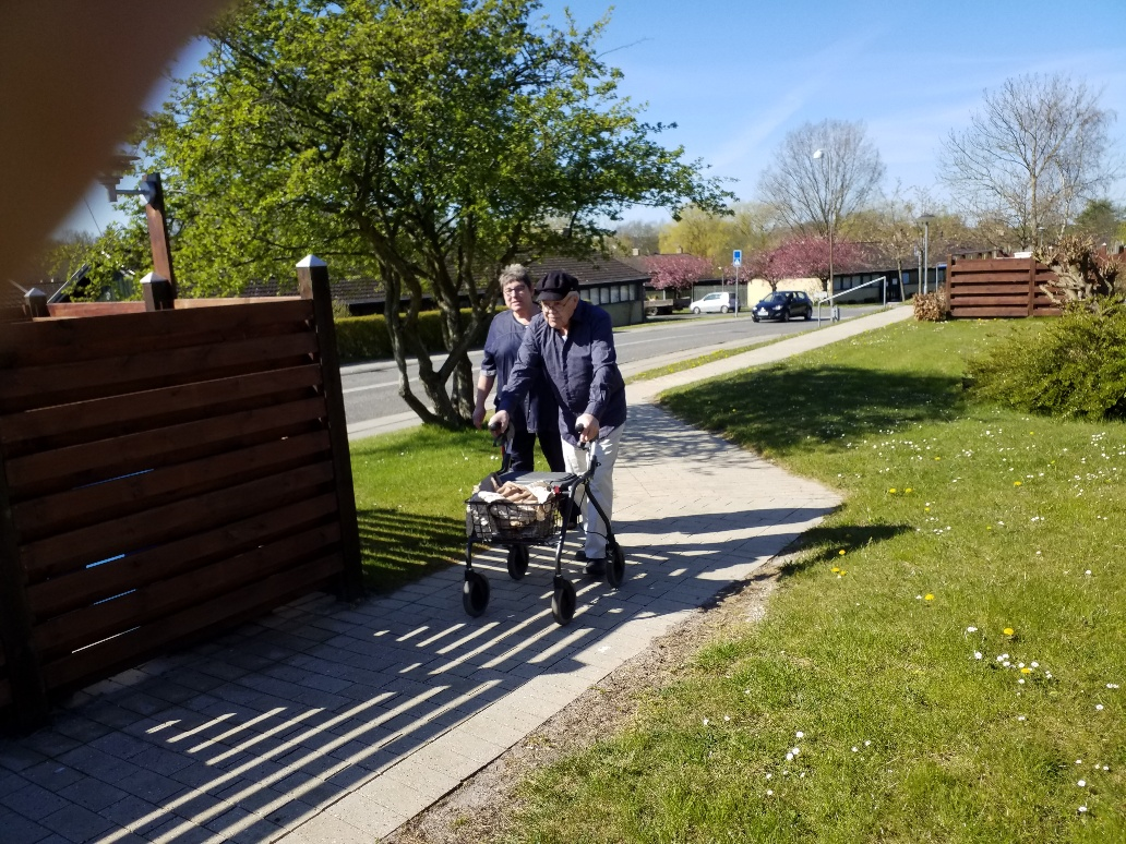 beboer med rollator på spadseretur med personale i coronatiden